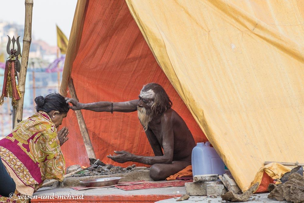 Sadhu segnet eine Pilgerin in Varanasi