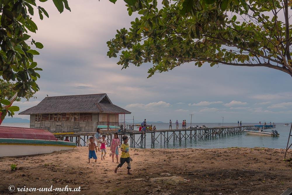Kinder spielen am Strand von Mabul