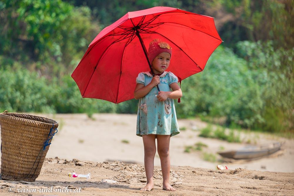 kleines Mädchen mit rotem Sonnenschirm am Mekong Ufer