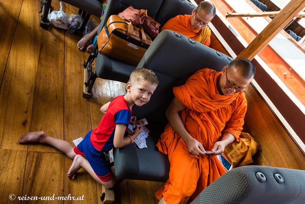 Kleiner französischer Junge mit Mönch beim Kartenspielen