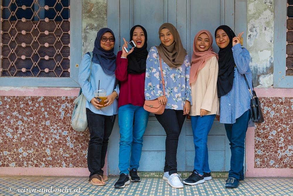 Fröhliche Mädchen posieren vor der Kamera in Georgetown, Penang